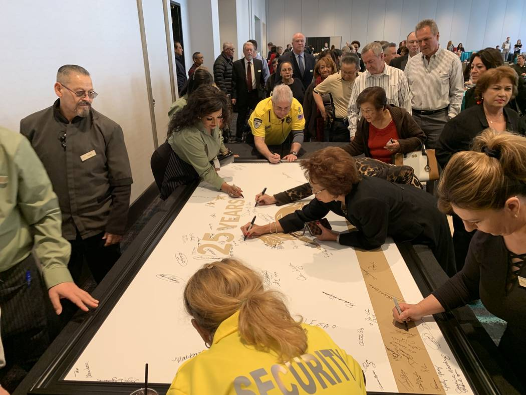 Some of the 784 MGM Grand employees that have worked at the property since the day it opened sign a poster to commemorate their 25th anniversary at the MGM Grand Conference Center in Las Vegas, Fr ...