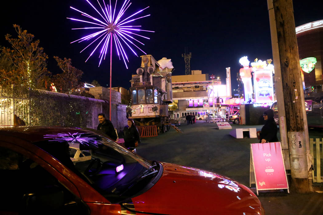 A Lyft ride picks up a couple as security guard Jennifer Fox , right, looks on at the Lyft Art Park in downtown Las Vegas Friday, Dec. 28, 2018. K.M. Cannon/Las Vegas Review-Journal @kmcannonphoto
