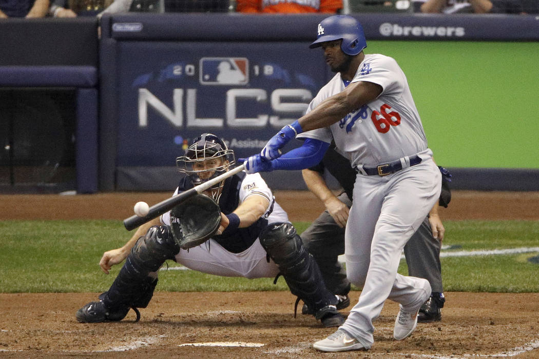 In this Oct. 20, 2018, file photo, Los Angeles Dodgers' Yasiel Puig (66) hits a three -run home run during the sixth inning of Game 7 of the National League Championship Series baseball game again ...