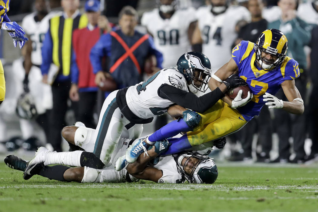 Los Angeles Rams wide receiver Robert Woods, right, is tackled by Philadelphia Eagles free safety Corey Graham, top, and cornerback Cre'von LeBlanc during the first half in an NFL football game Su ...