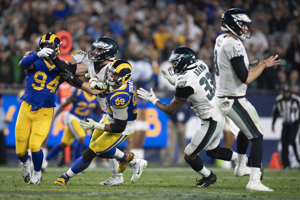 Los Angeles Rams defensive end Aaron Donald, second from left, chases Philadelphia Eagles quarterback Nick Foles in an NFL football game Sunday, Dec. 16, 2018, in Los Angeles. (AP Photo/Kyusung Gong)