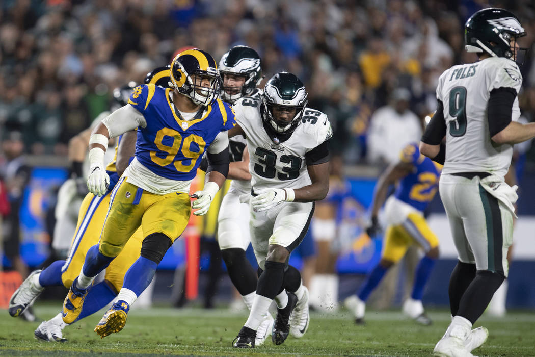 Los Angeles Rams defensive end Aaron Donald, left, chases Philadelphia Eagles quarterback Nick Foles in an NFL football game Sunday, Dec. 16, 2018, in Los Angeles. (AP Photo/Kyusung Gong)