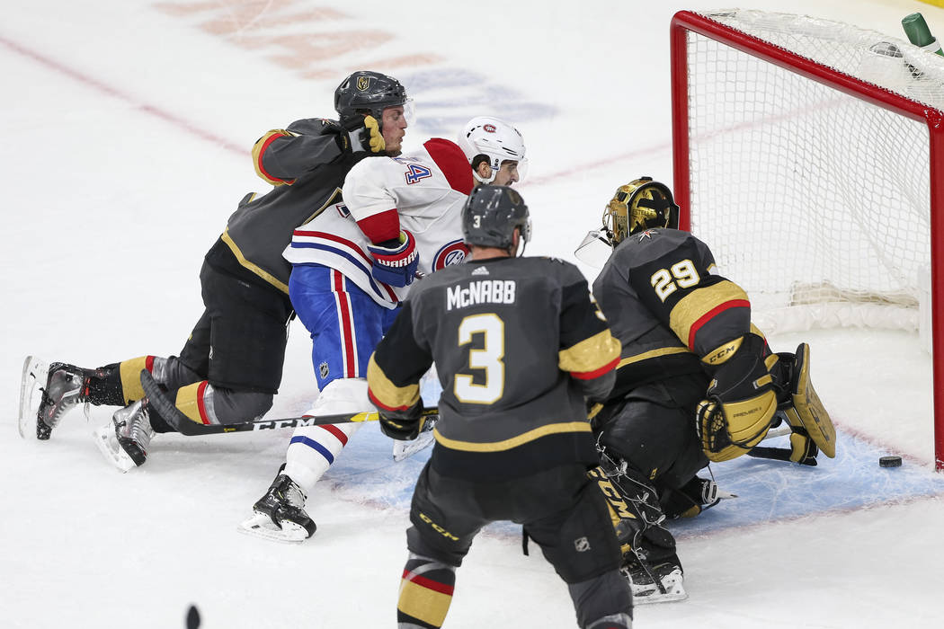 Vegas Golden Knights defenseman Nate Schmidt (88), left, crashes into Montreal Canadiens center Phillip Danault (24), center, as Danault scores a goal against Knights goaltender Marc-Andre Fleury ...