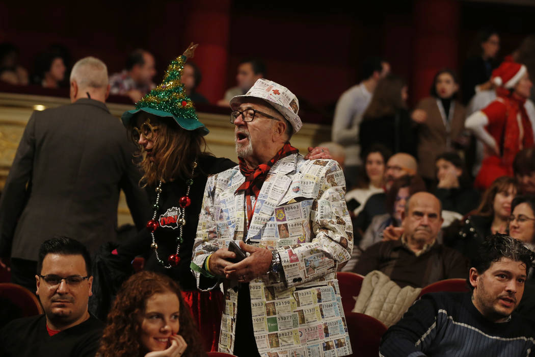 A man wearing a suit jacket made of lottery tickets arrives before the draw at Madrid's Teatro Real opera house during Spanish Christmas Lottery draw in Madrid, Spain, Saturday, Dec. 22, 2018. (AP ...