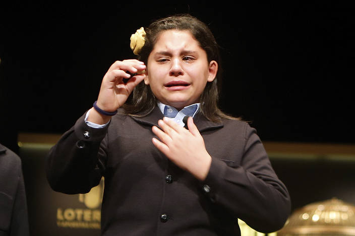 A girl from Madrid's San Ildefonso school cries after picking out one of lottery winners at Madrid's Teatro Real opera house during Spanish Christmas Lottery draw in Madrid, Spain, Saturday, Dec. ...