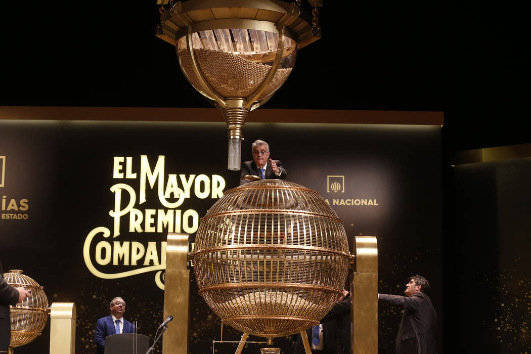 A worker supervises the lottery balls to be drawn at Madrid's Teatro Real opera house during Spanish Christmas Lottery draw in Madrid, Spain, Saturday, Dec. 22, 2018. (AP Photo/Paul White)