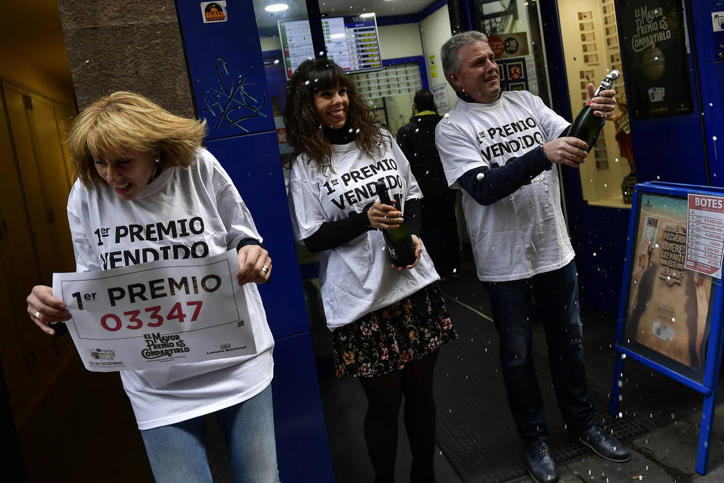 Tomas Arizta, a owner of a lottery office, celebrates with sparkling wine beside Asuncion Daguerrea and Edurne Gomez, center, after selling the first prize Christmas lottery ticket El Gordo, or Th ...