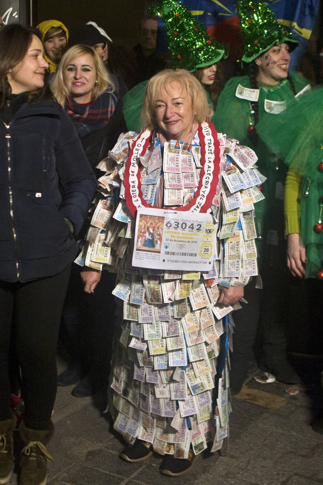 A woman wearing a costume of lottery tickets arrives before the draw at Madrid's Teatro Real opera house during Spanish Christmas Lottery draw in Madrid, Spain, Saturday, Dec. 22, 2018. (AP Photo/ ...