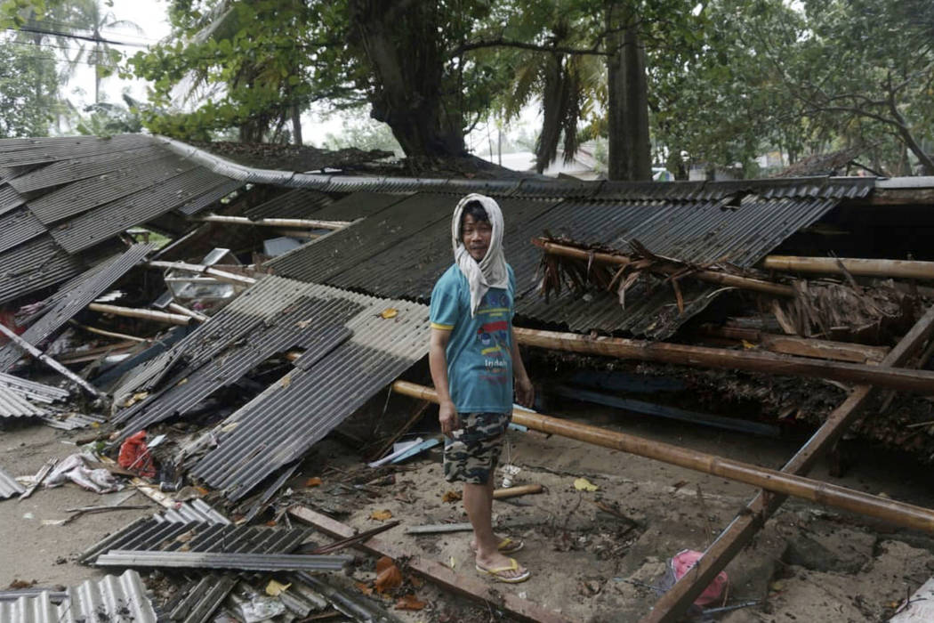 A man inspects his house which was damaged by a tsunami, in Carita, Indonesia, Sunday, Dec. 23, 2018. (AP Photo/Dian Triyuli Handoko)