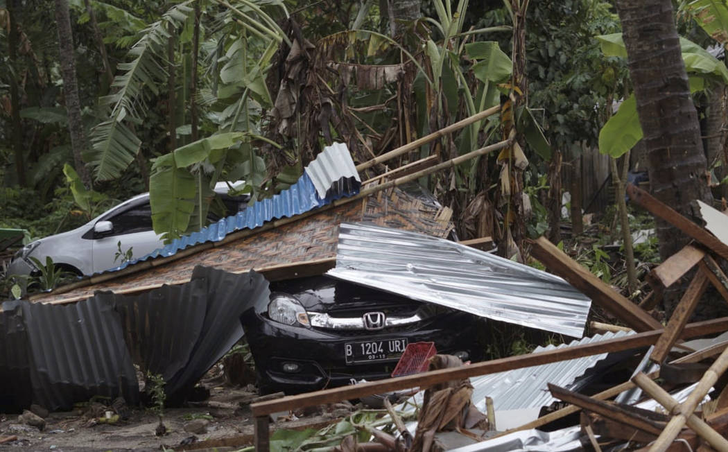 Cars are covered by debris at an area ravaged by a tsunami, in Carita, Indonesia, Sunday, Dec. 23, 2018. (AP Photo/Dian Triyuli Handoko)