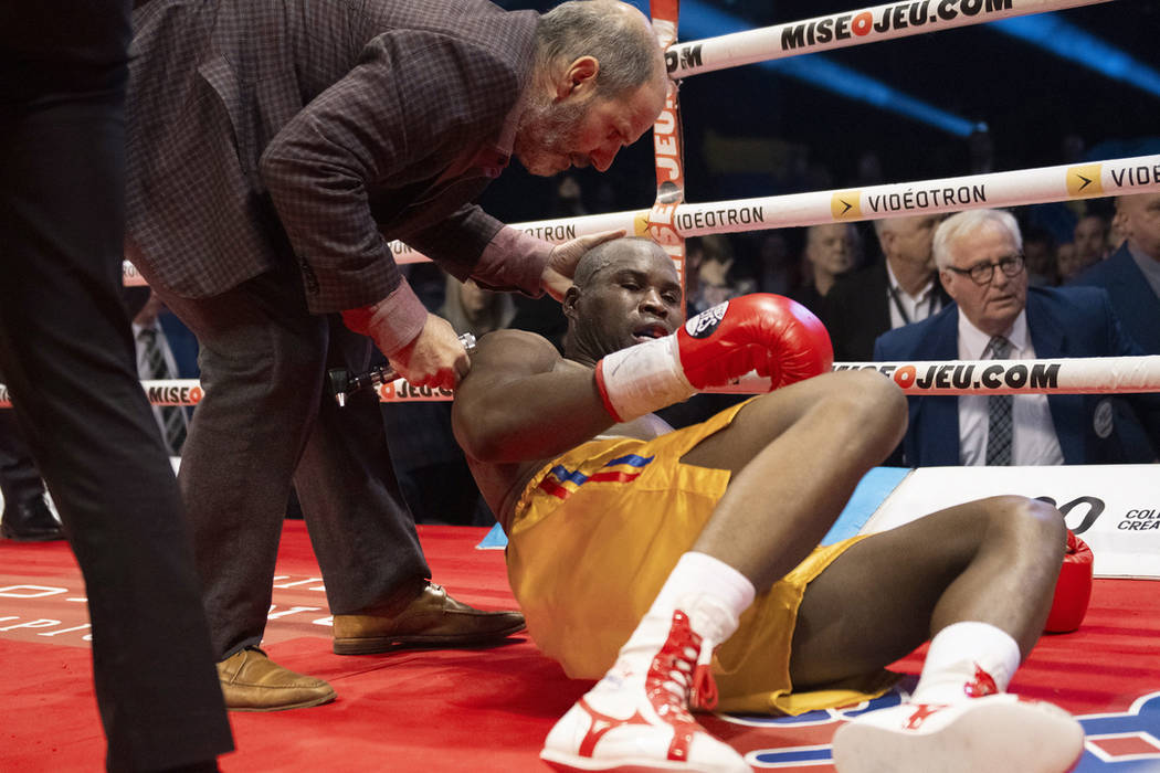 Ring doctor Marc Gagne, left, checks on Adonis Stevenson, of Canada, after he was knocked out by Oleksandr Gvozdyk, of Ukraine, in their light heavyweight WBC championship boxing fight, Saturday, ...