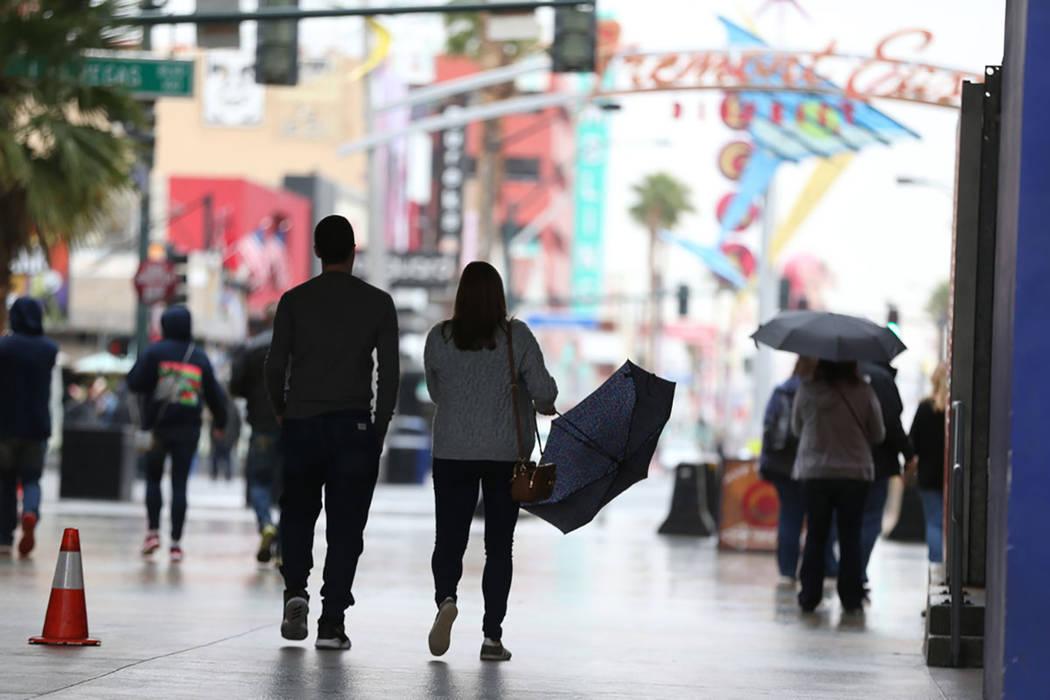 People walk in downtown Las Vegas as rain falls. (Erik Verduzco Las Vegas Review-Journal @Erik_Verduzco)
