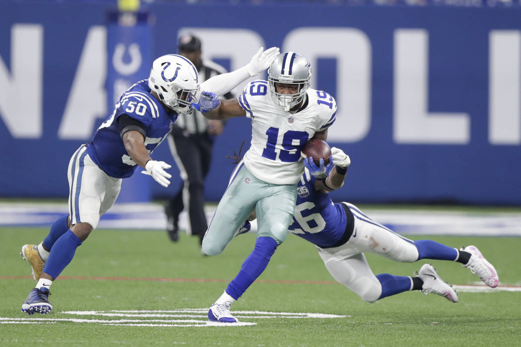 Dallas Cowboys wide receiver Amari Cooper (19) is tackled by Indianapolis Colts' Anthony Walker (50) and Clayton Geathers (26) during the first half of an NFL football game, Sunday, Dec. 16, 2018, ...