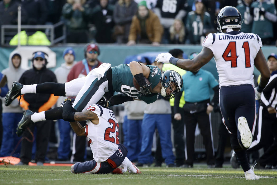Philadelphia Eagles' Zach Ertz (86) is tackled by Houston Texans' Aaron Colvin (22) as Zach Cunningham (41) runs in during the first half of an NFL football game, Sunday, Dec. 23, 2018, in Philade ...