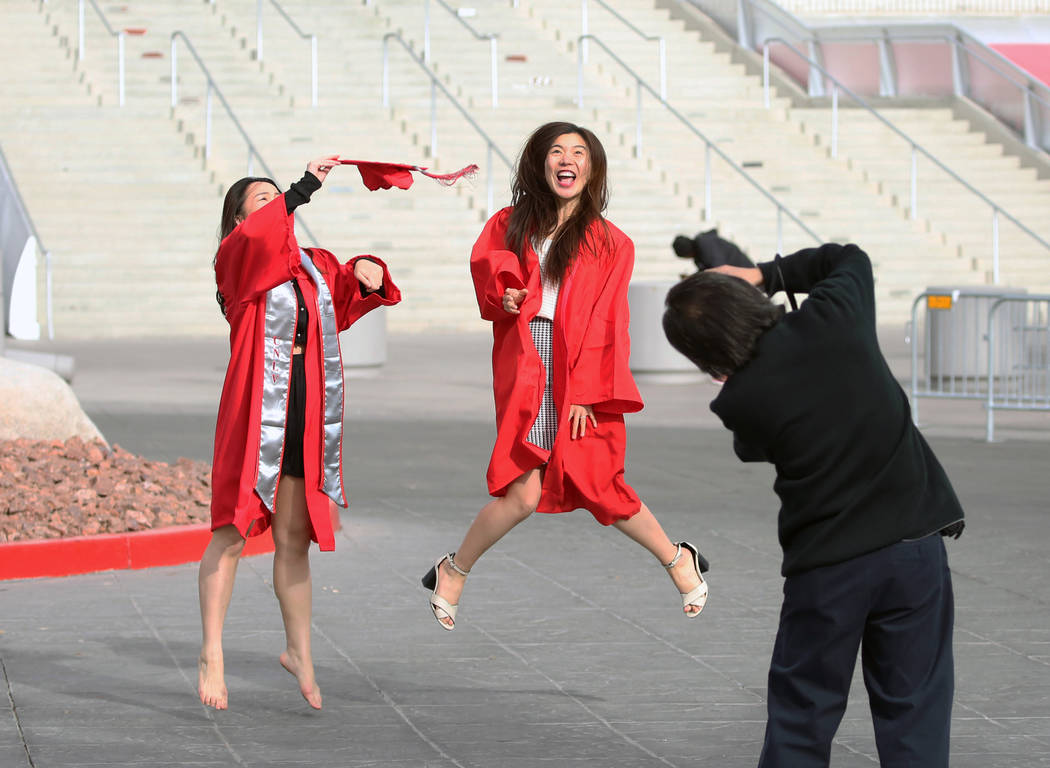 UNLV accounting student Qumin Ku, left, and nursing student Ping Li, both of China, pose for Chris Chow of Las Vegas as they rehearse for their graduation pose outside Thomas and Mack Center on Mo ...