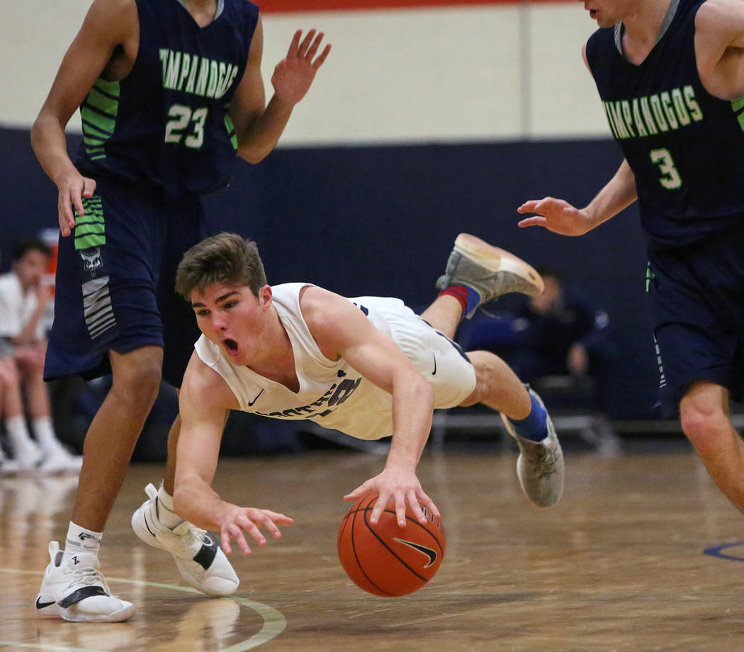 Foothill's Fisher Welch (12) falls to the ground with the ball while under pressure from Timpanogos' Michael Kennerly (23), left, and Riley Curtis (3) during the second half of a Tarkanian Classic ...