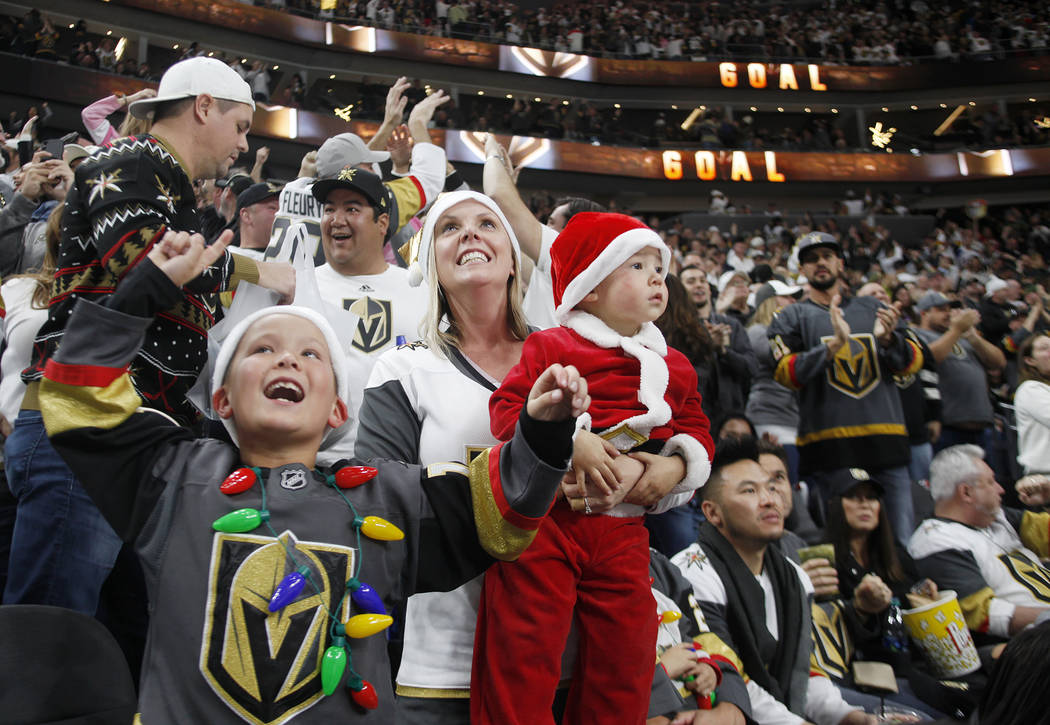 The Tra family, from left, Tyson Tra, 7, Gabrielle Tra and Tatum Tra, 2, cheer after the Vegas Golden Knights scored against the Los Angeles Kings in the second period at T-Mobile Arena in Las Veg ...