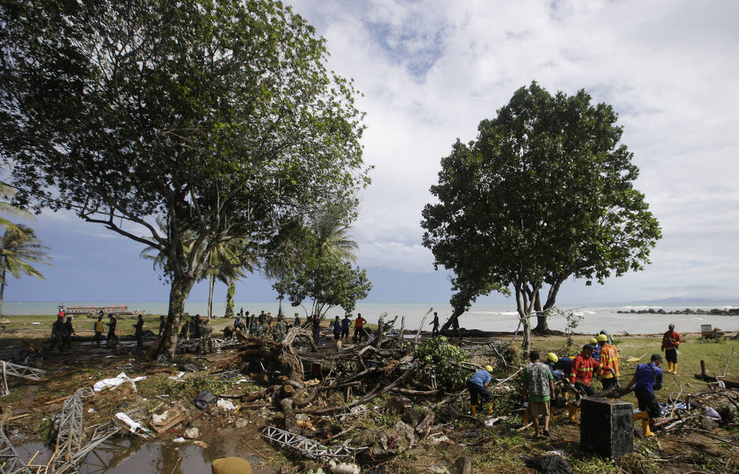 Indonesian soldiers and rescue team search the bodies of tsunami victims at a beach resort in Tanjung Lesung, Indonesia, Monday, Dec. 24, 2018. Doctors are working to help survivors and rescuers a ...