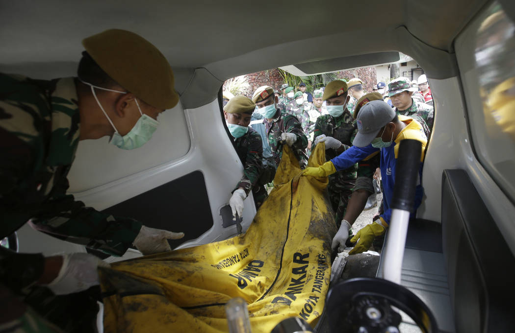 Indonesian soldiers load the body of a tsunami victim into an ambulance at Tanjung Lesung beach resort, Indonesia, Monday, Dec. 24, 2018. Doctors are working to help survivors and rescuers are loo ...
