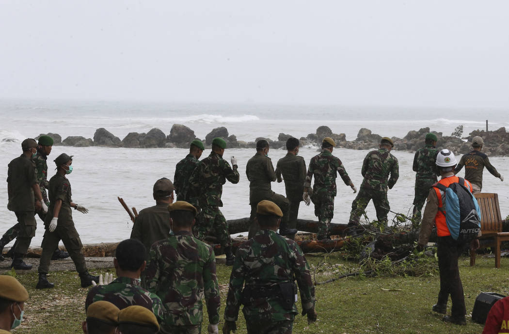 Indonesian soldiers and rescue team search the tsunami victims at a beach resort in Tanjung Lesung, Indonesia, Monday, Dec. 24, 2018. Doctors are working to help survivors and rescuers are looking ...