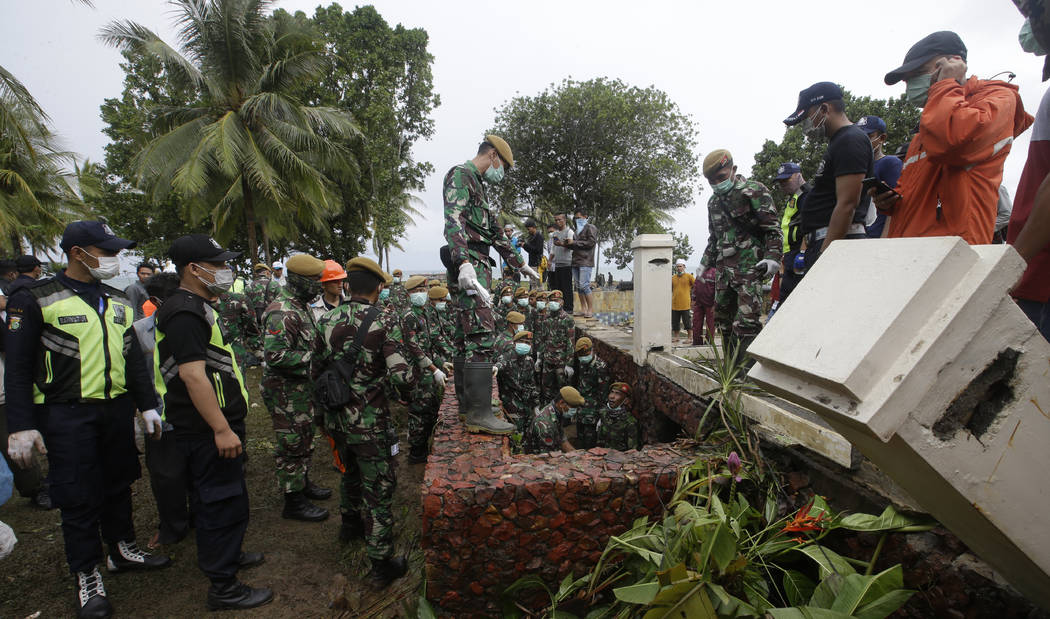 Indonesian soldiers and rescuers search the tsunami victims at a beach resort in Tanjung Lesung, Indonesia, Monday, Dec. 24, 2018. Doctors are working to help survivors and rescuers are looking fo ...