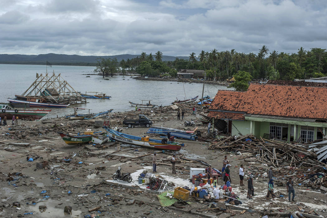 People inspect the damage at a tsunami-ravaged village in Sumur, Indonesia, Monday, Dec. 24, 2018. Doctors worked to save injured victims while hundreds of military and volunteers scoured debris-s ...