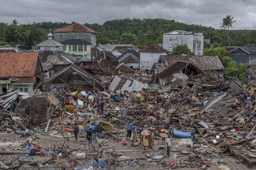 People inspect the damage at a tsunami-ravaged village in Sumur, Indonesia, Monday, Dec. 24, 2018. Doctors are working to help survivors and rescuers are looking for more victims from a deadly tsu ...