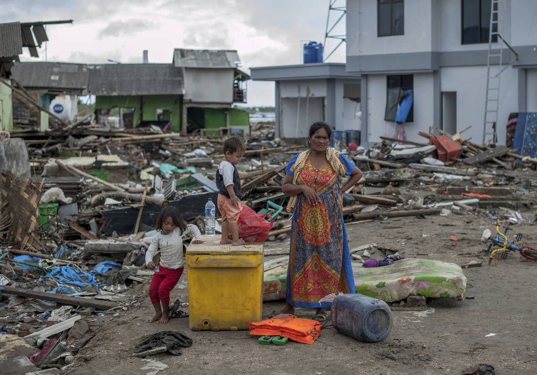 A woman and her children inspect the damage at a tsunami-ravaged village in Sumur, Indonesia, Monday, Dec. 24, 2018.Doctors worked to save injured victims while hundreds of military and volunteers ...