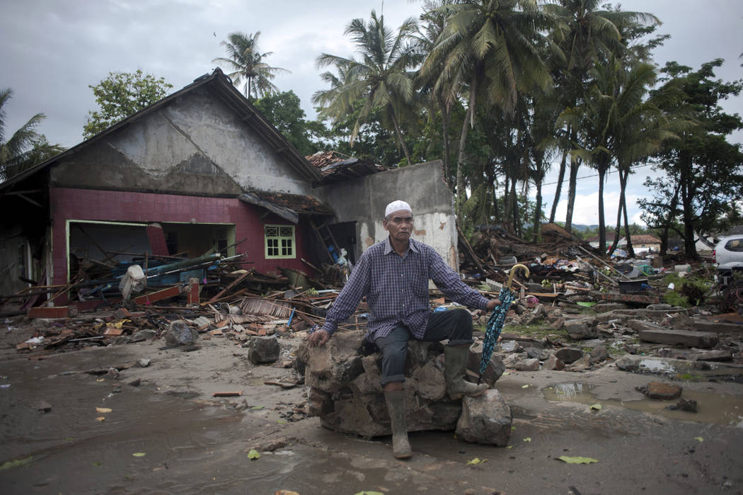 A man sits on a piece of debris at a tsunami-ravaged village in Sumur, Indonesia, Monday, Dec. 24, 2018. Doctors worked to save injured victims while hundreds of military and volunteers scoured de ...