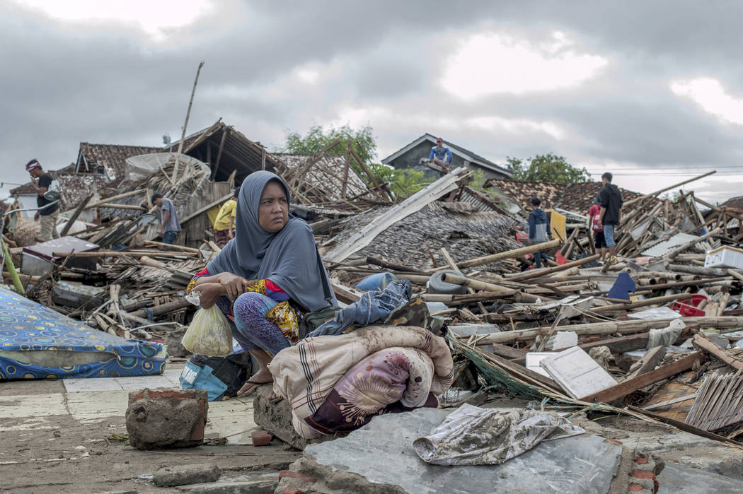 A tsunami survivor sits on a pice of debris as she salvages items from the location of her house in Sumur, Indonesia, Monday, Dec. 24, 2018. Doctors worked to save injured victims while hundreds o ...