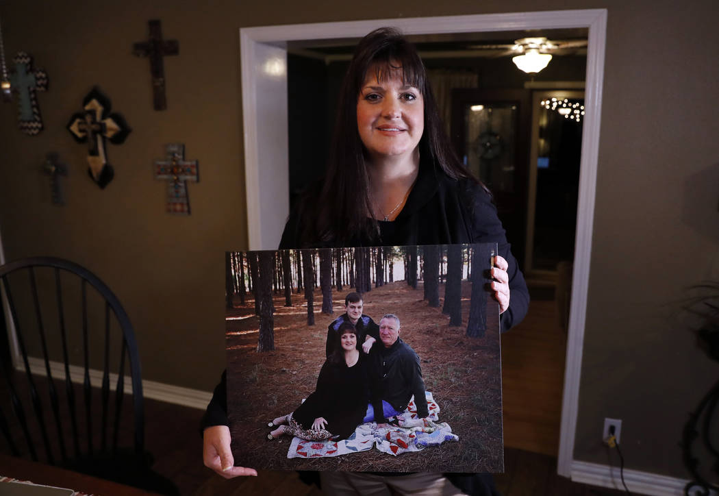 In this Thursday, Dec. 20, 2018 photo, Reagen Adair poses for a photo at her home holding a portrait of herself, with her husband Dale and son Mason, in Murchison, Texas. Adair, a fifth-grade teac ...