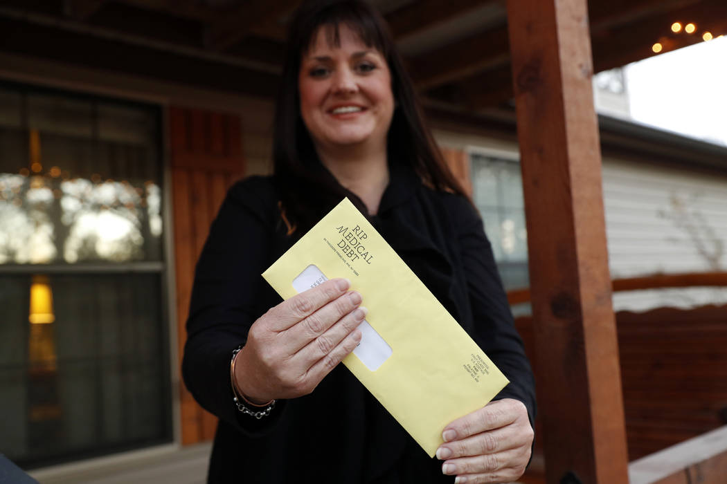 In this Dec. 20, 2018 photo, Reagen Adair holds on to an RIP Medical Debt yellow envelope as she poses for a photo at her home in Murchison, Texas. The co-founders of RIP Medical Debt buy millions ...
