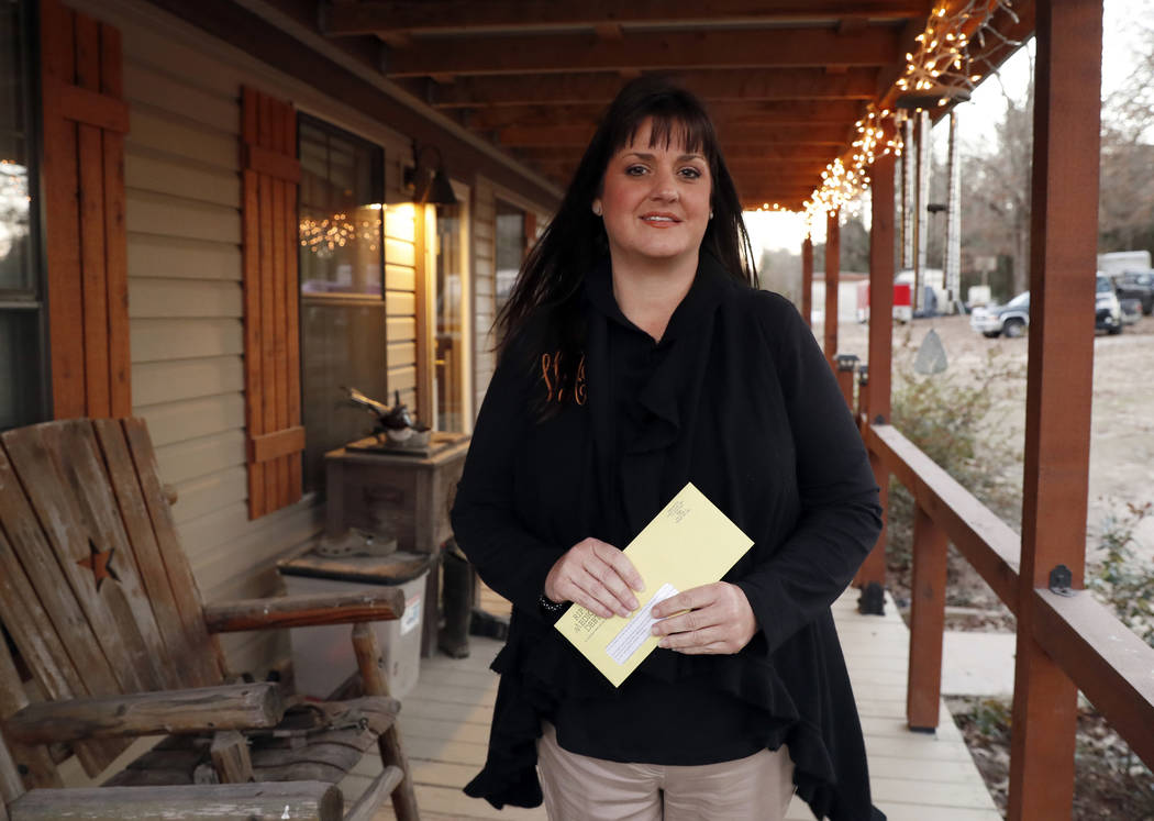 In this Thursday, Dec. 20, 2018 photo, Reagen Adair holds on to a RIP Medical Debt yellow envelope as she poses for a photo at her home in Murchison, Texas. The co-founders of RIP Medical Debt buy ...
