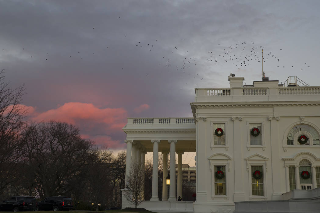 the setting sun illuminates clouds behind the white house during a partial federal shutdown saturday