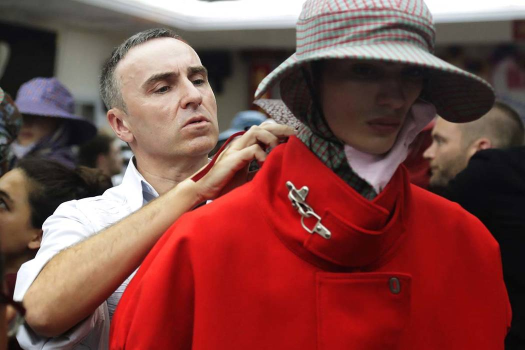 Fashion designer Raf Simons, left, makes adjustments before his fashion show during Men's Fashion Week in New York on Tuesday, July 11, 2017. Simons is parting ways with Calvin Klein after two yea ...