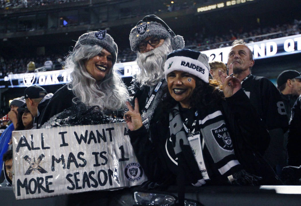 Oakland Raiders fans hold up a sign on what could be the team's last game at the Oakland-Alameda County Coliseum during the first half of an NFL game against the Denver Broncos in Oakland, Calif., ...