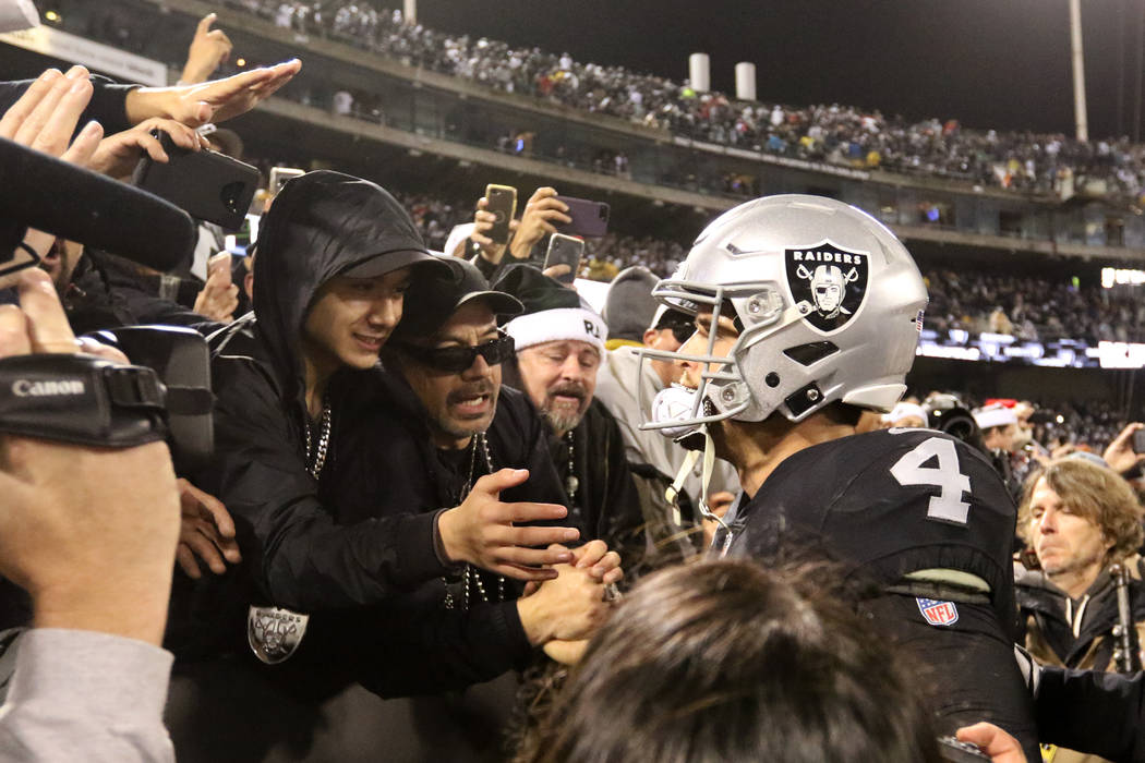 Oakland Raiders quarterback Derek Carr (4) meets with fans in the Black Hole in the Oakland-Alameda County Coliseum field after the team's win over the against the Denver Broncos in Oakland, Calif ...