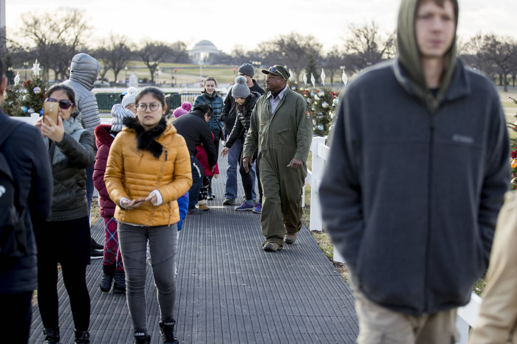 A National Park Service employee directs visitors to the exit at the National Christmas Tree on the Ellipse near the White House, Monday, Dec. 24, 2018, in Washington. The area was reopened after ...