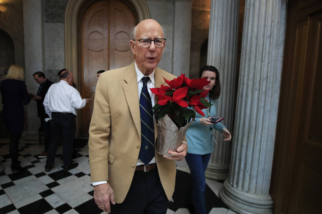 Sen. Pat Roberts, R-Kan., carries a poinsettia on Capitol Hill in Washington, Monday, Dec. 24, 2018, after a pro forma session, a brief meeting of the Senate, during a partial government shutdown. ...
