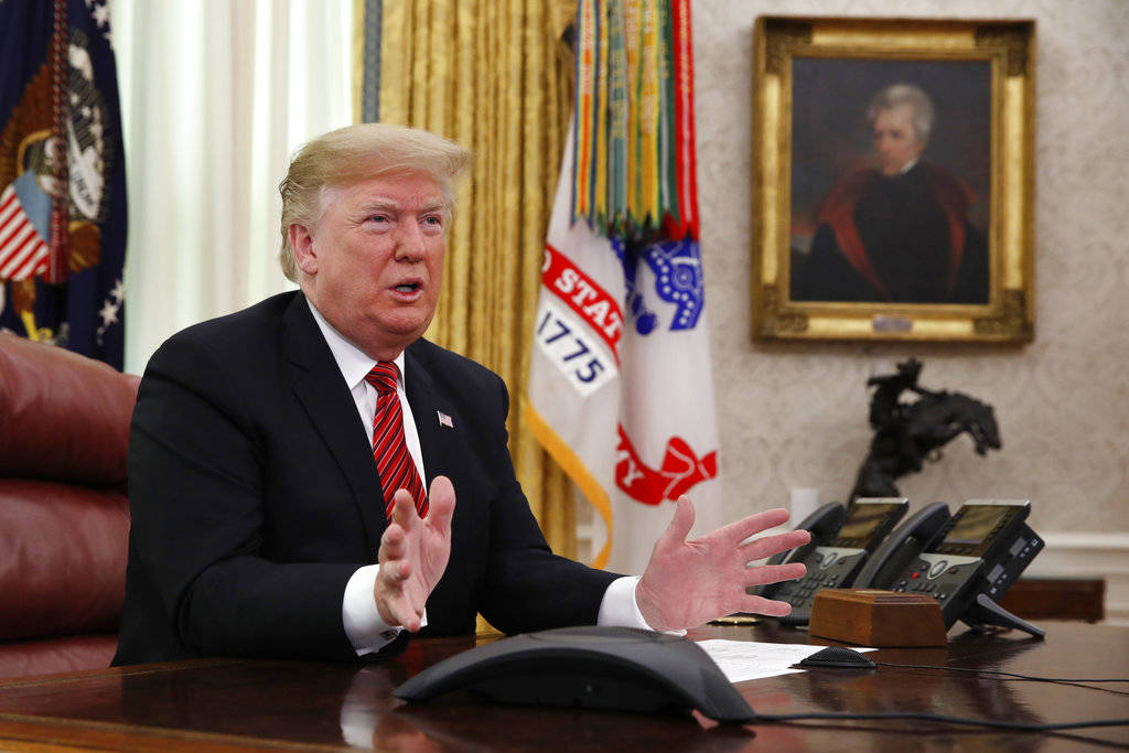 President Donald Trump greets members of the five branches of the military by video conference on Christmas Day, Tuesday, Dec. 25, 2018, in the Oval Office of the White House. The military members ...