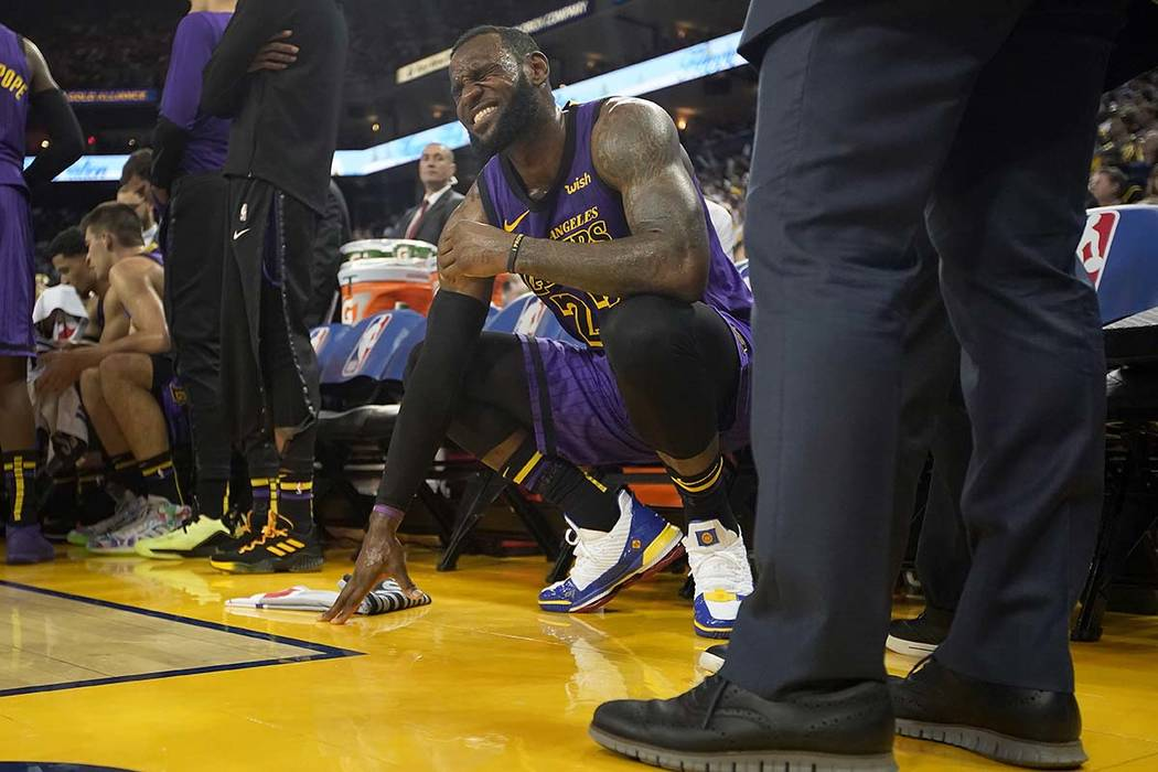 Los Angeles Lakers forward LeBron James grimaces after injuring his left groin, during the second half of the team's NBA basketball game against the Golden State Warriors on Tuesday, Dec. 25, 2018 ...