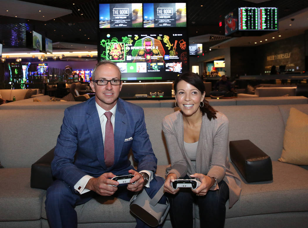 Christian Stuart, left, Caesars Entertainment's executive vice president, Gaming and Interactive Entertainment, and Jennifer Forkish, vice president communications, play Xbox one at the LINQ's gam ...