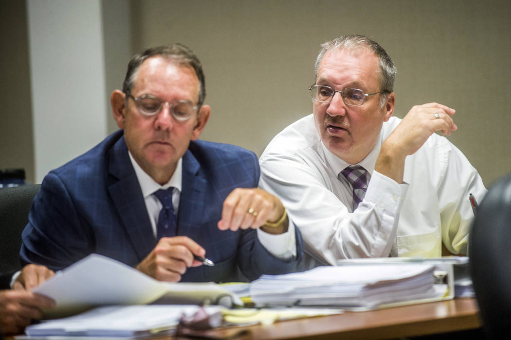 In this Aug. 22, 2018, file photo, Defendant Michael Prysby looks over paperwork with his defense attorneys at Genesee District Court in Flint, Mich. Prysby and Stephen Busch, two Michigan environ ...