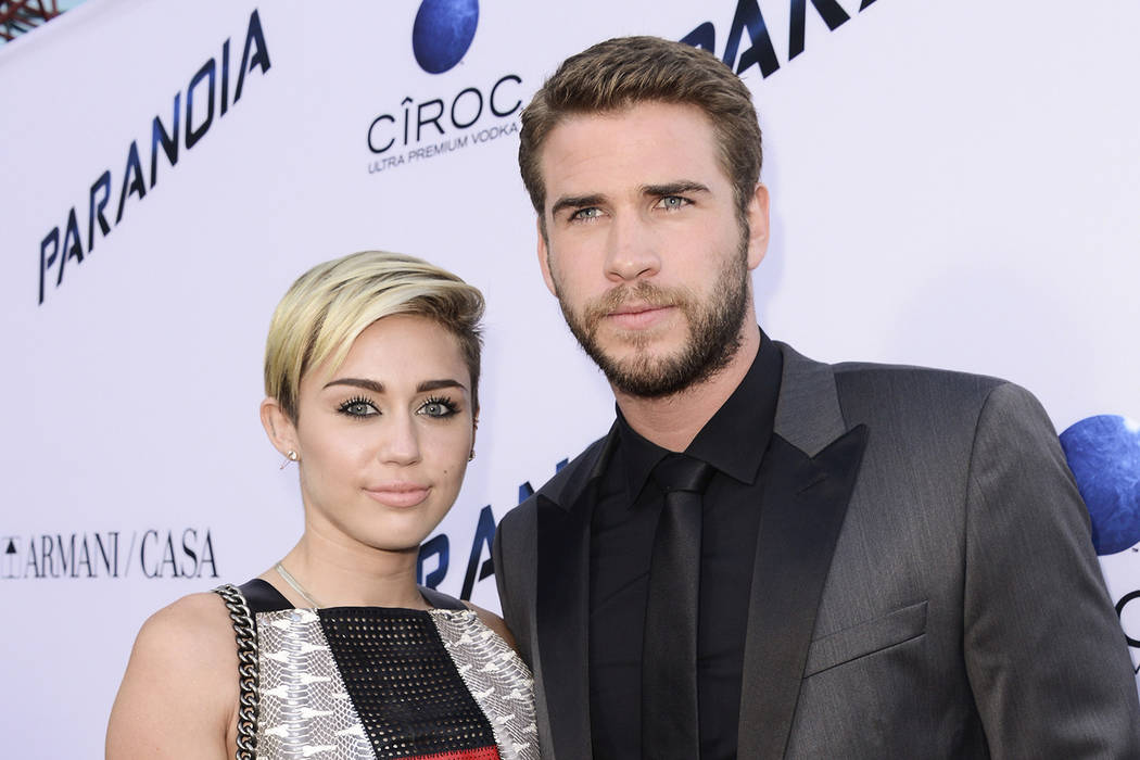 """In this Aug. 8, 2013, file photo, actor Liam Hemsworth and singer and actress Miley Cyrus arrive on the red carpet at the US premiere of the feature film """"Paranoia"""" at the DGA Theatre in Los Angel ..."""