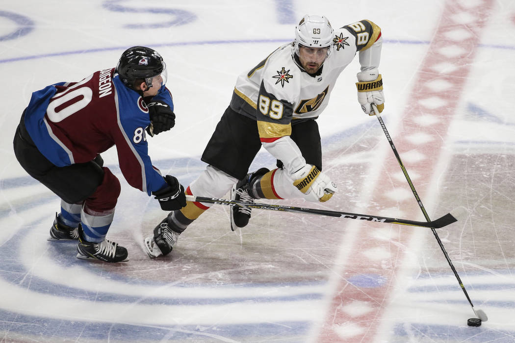 Vegas Golden Knights right wing Alex Tuch (89) moves the puck past Colorado Avalanche center Brandon Saigeon (80) during the first period of a preseason NHL hockey game Tuesday, Sept. 18, 2018, in ...