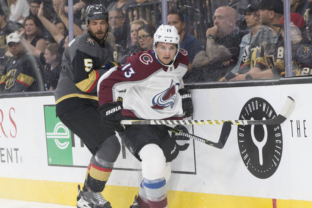 Colorado Avalanche center Alexander Kerfoot (13) fights for possession with Golden Knights defenseman Deryk Engelland (5)) in the first period during their NHL preseason matchup on Monday, Sept. 2 ...