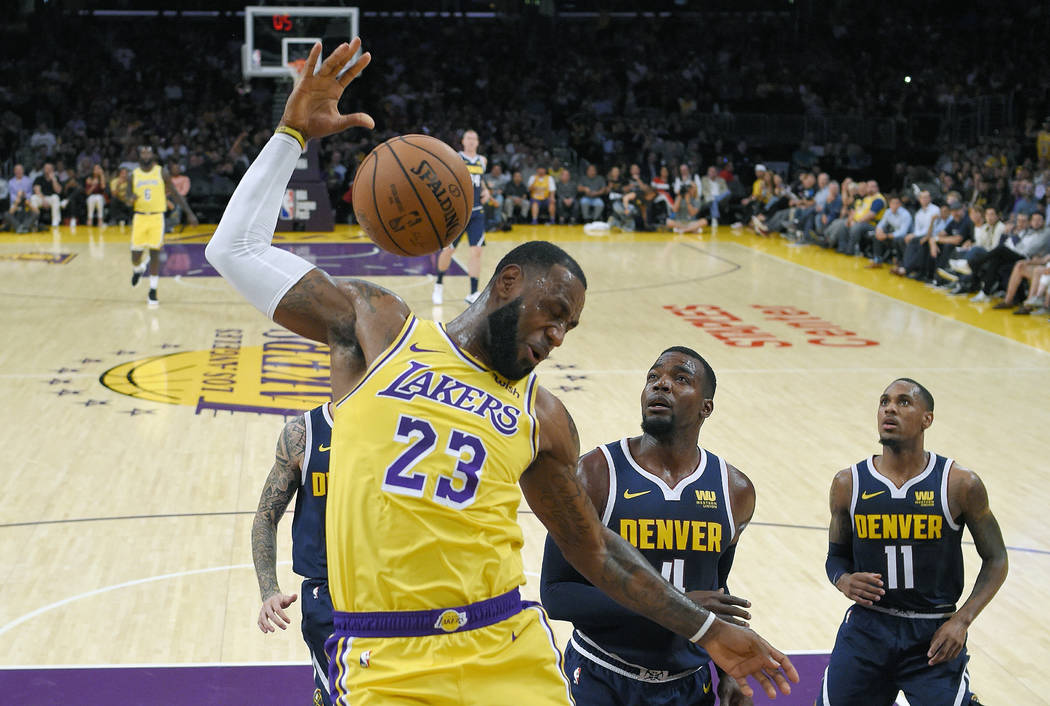 In this Tuesday, Oct. 2, 2018, file photo, Los Angeles Lakers forward LeBron James, left, follows through on a dunk as Denver Nuggets forward Paul Millsap, center, and guard Monte Morris watch dur ...