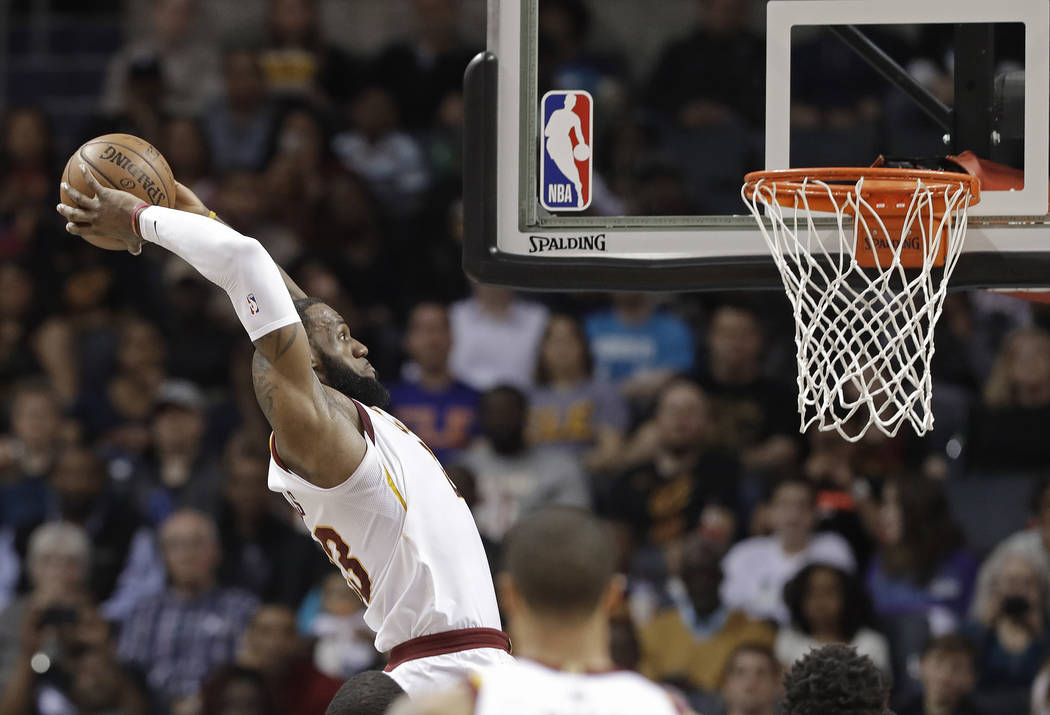 In this March 28, 2018, file photo, Cleveland Cavaliers' LeBron James goes up to dunk against the Charlotte Hornets during the first half of an NBA basketball game in Charlotte, N.C. (AP Photo/Chu ...