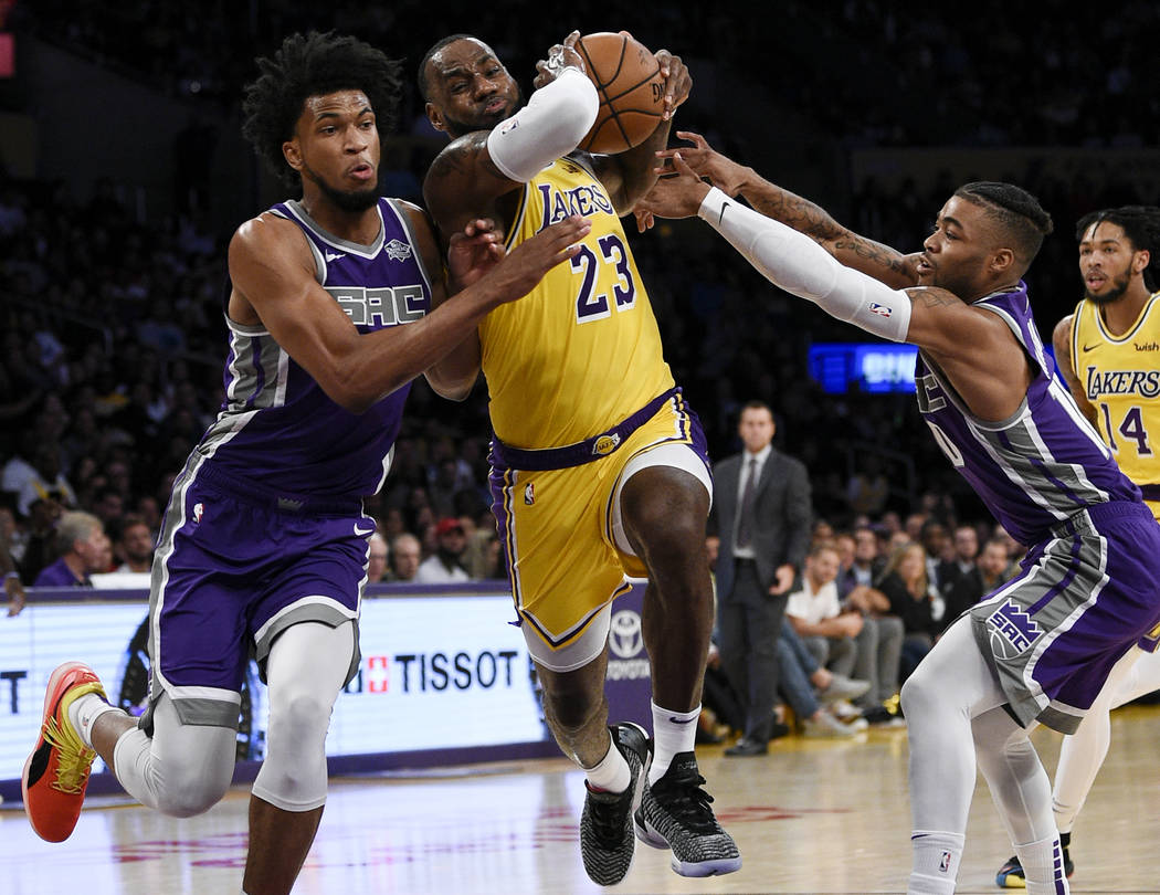 In this Oct. 4, 2018, file photo, Los Angeles Lakers forward LeBron James, center, drives between Sacramento Kings forward Marvin Bagley III, left, and guard Frank Mason III during the first half ...