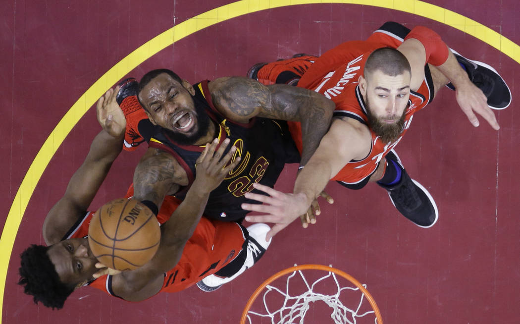 In this May 5, 2018, file photo, Cleveland Cavaliers' LeBron James (23) goes up for a shot between Toronto Raptors' OG Anunoby, left, and Jonas Valanciunas during the first half of Game 3 of an NB ...